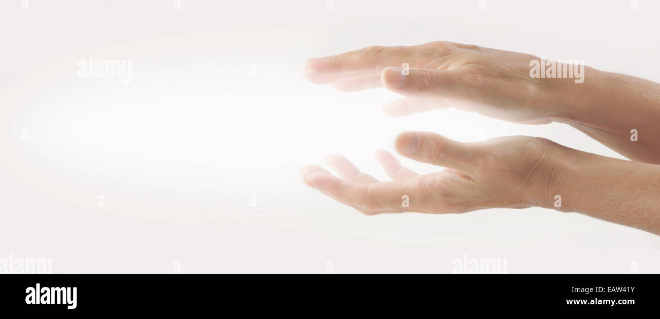 Beaming Reiki Healing Energy  -  Pair of female hands held parallel on a light background with white energy between - Stock Image