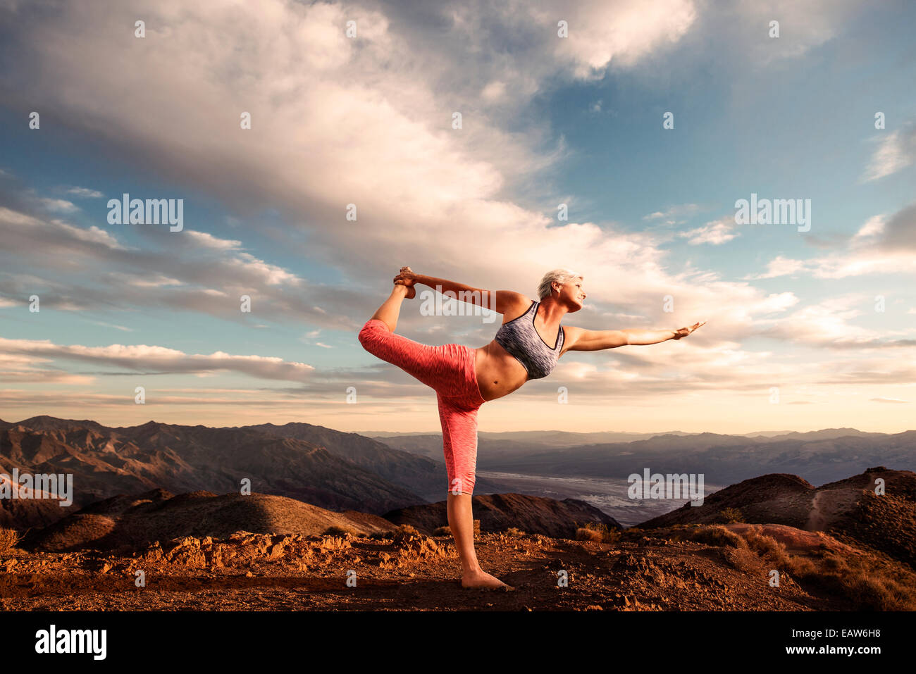 Senior woman doing yoga pose on top of mountain at sunset with landscape and desert valley below. Stock Photo