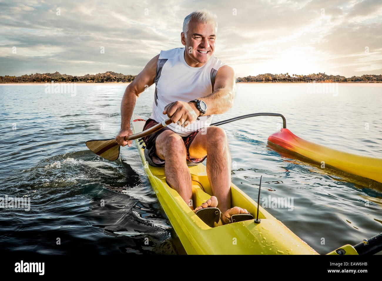 Senior man paddling outrigger canoe in the ocean at sunrise with tropical island behind him. - Stock Image