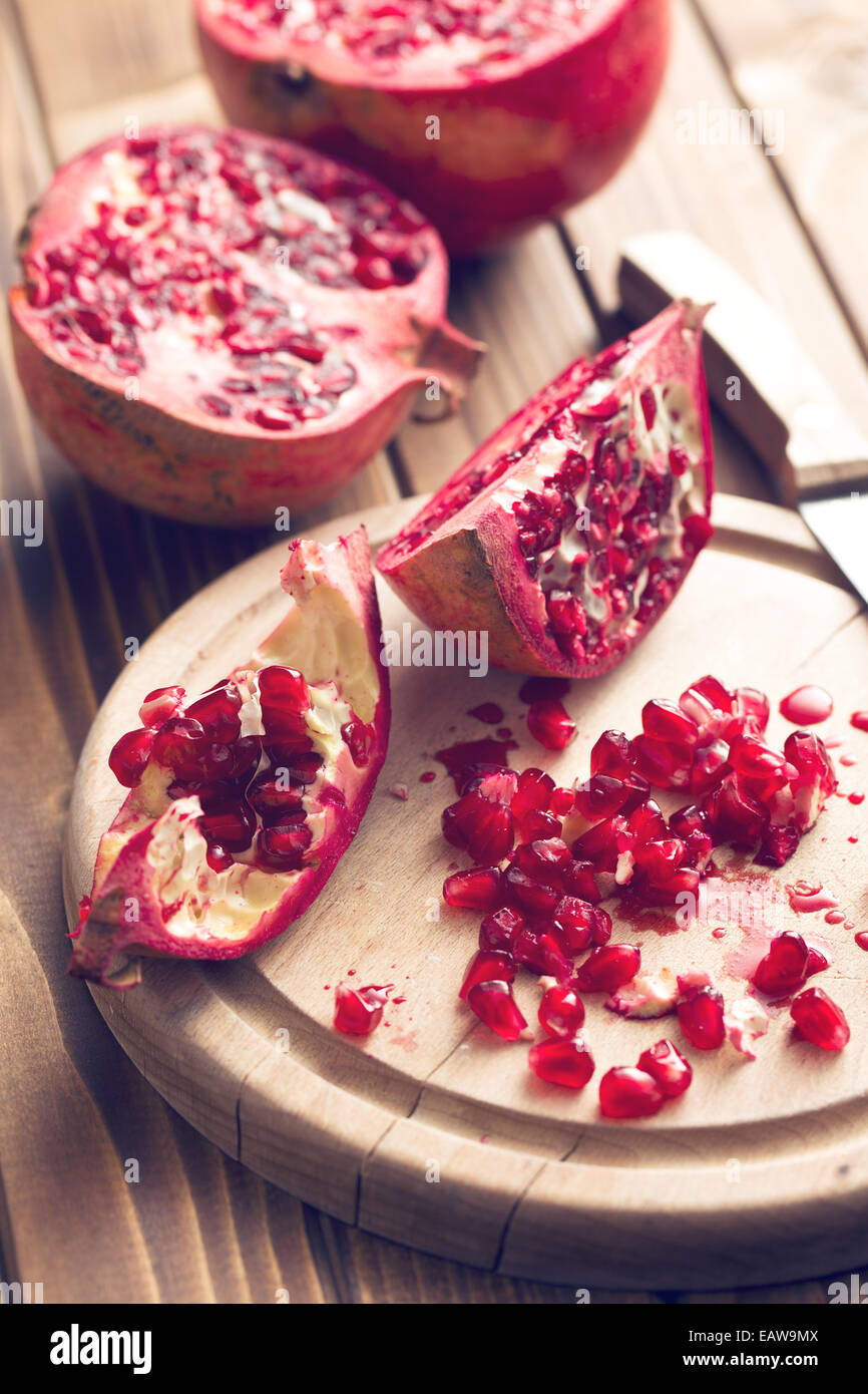 red pomegranate on wooden table - Stock Image