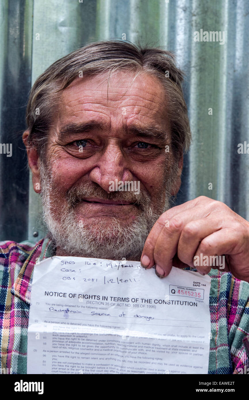 A displaced man holds fines issued by police for begging in Pretoria. - Stock Image