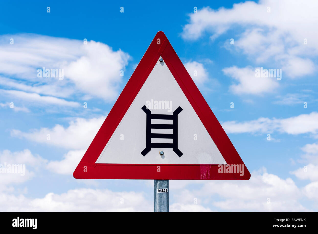 A sign warning of the danger of an upcoming railway crossing. - Stock Image