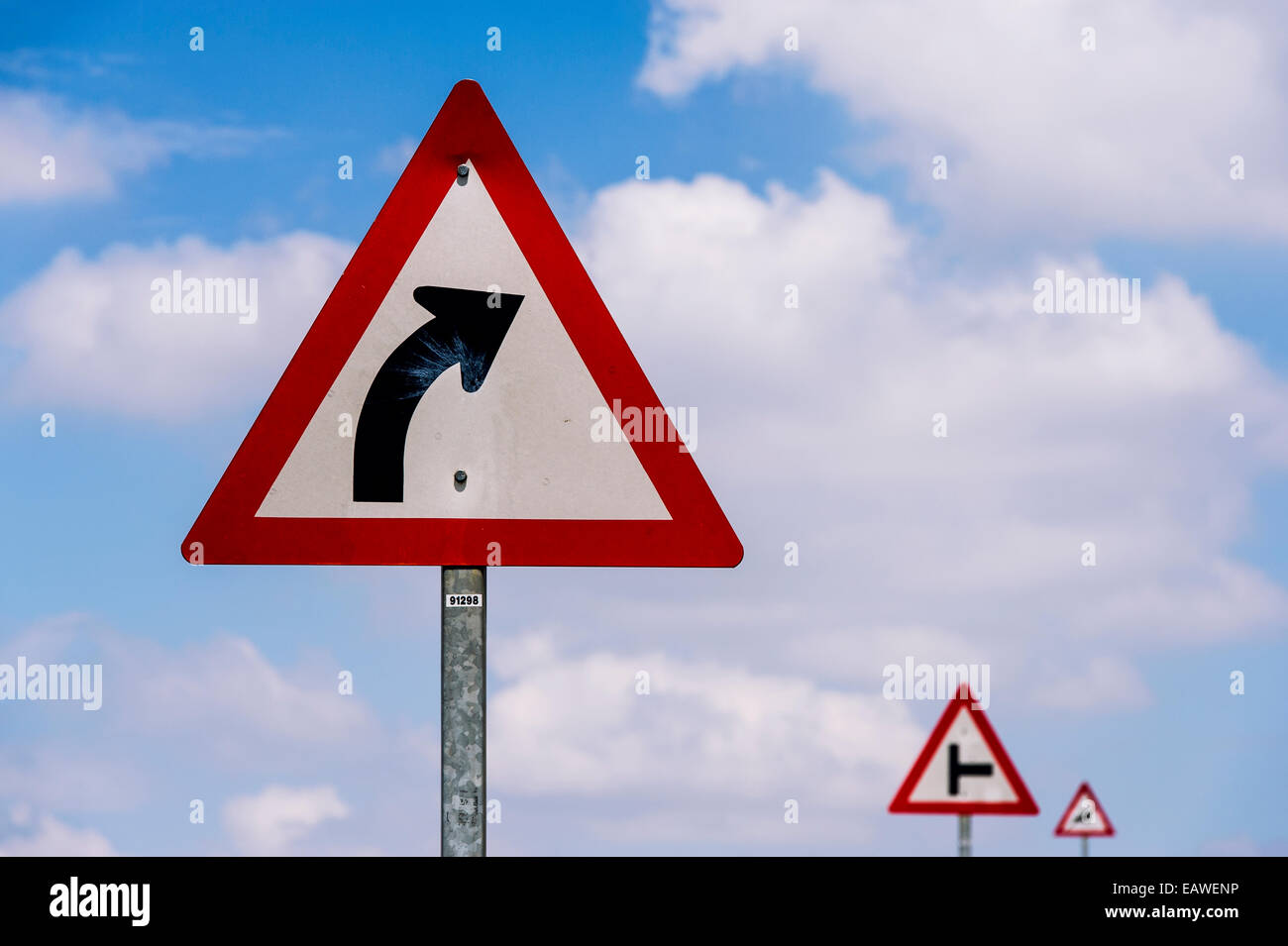 A series of signs warn of impending driving hazards and dangers. - Stock Image