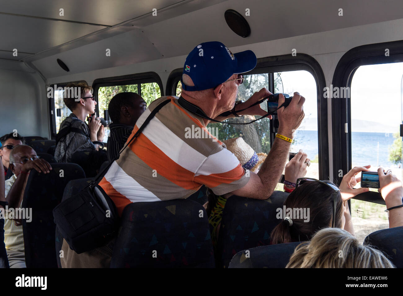 Tourists photograph historical prison museum sites from a tour bus. - Stock Image