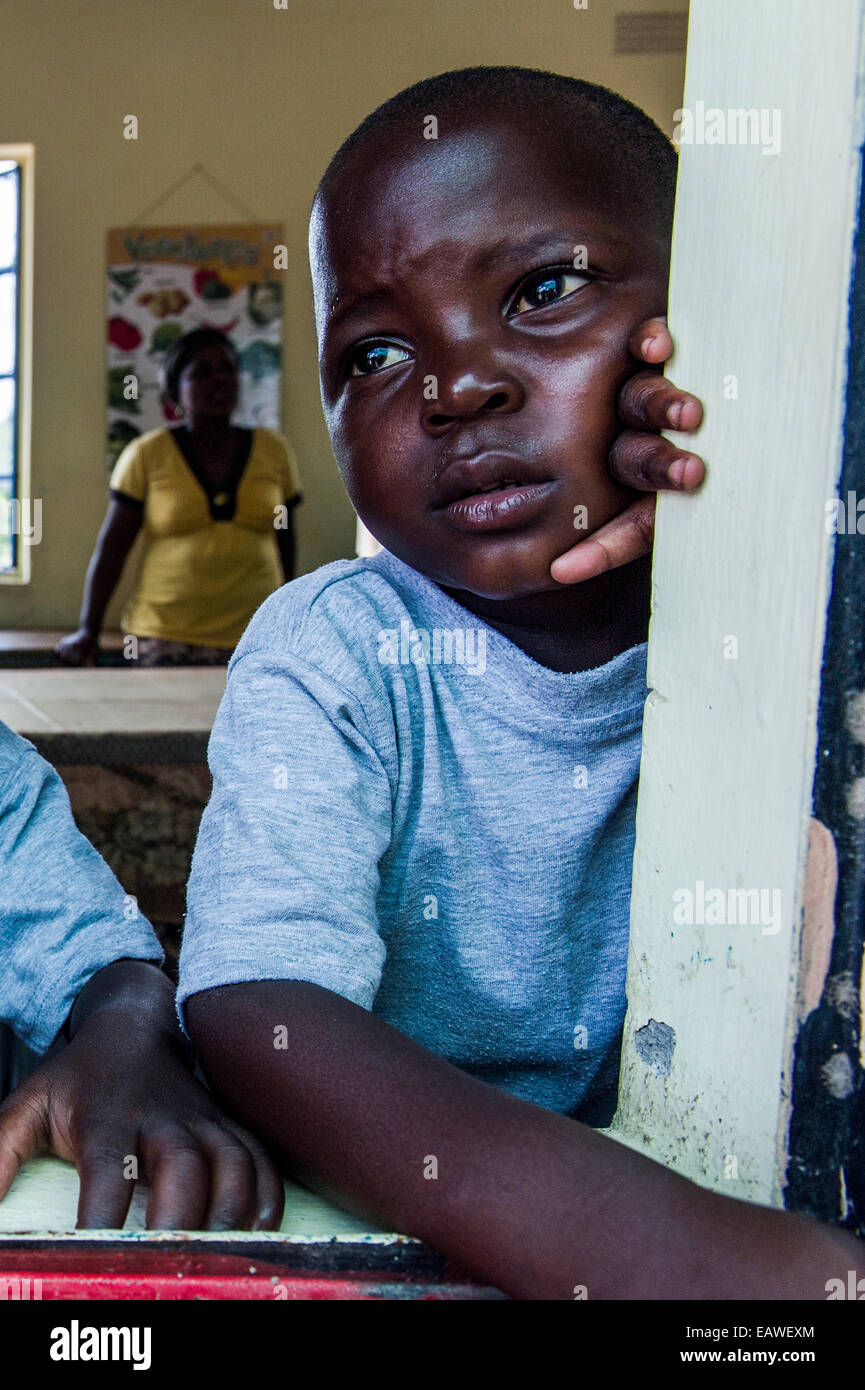 A boy looks out through a classroom window in a small African school. - Stock Image