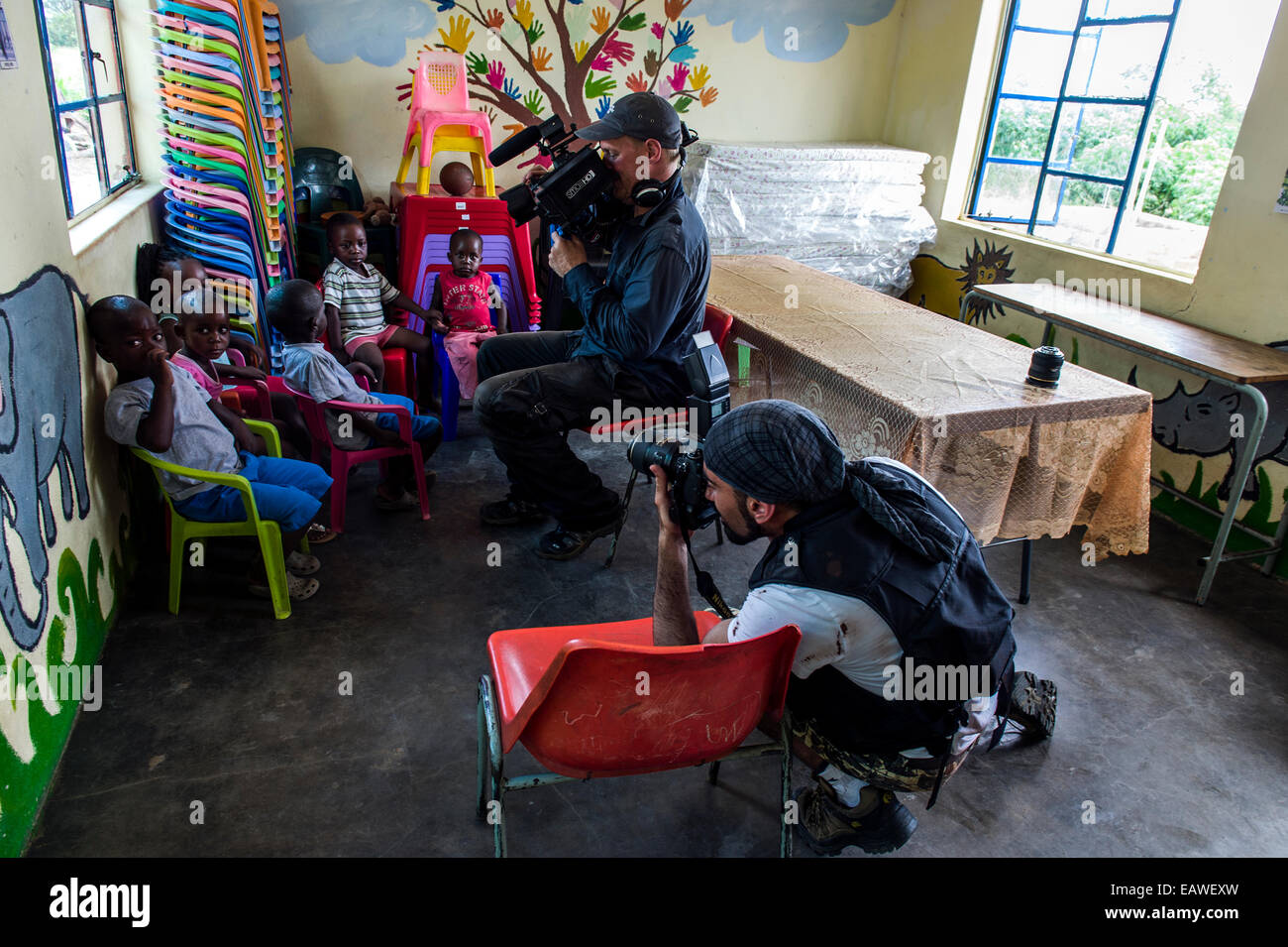 A film crew photographs children in a small African Primary school. - Stock Image