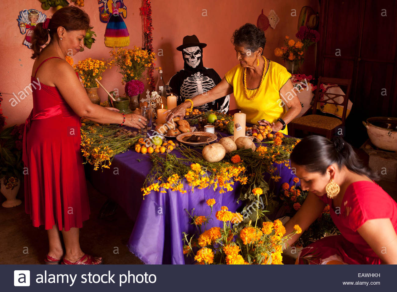 Women arrange marigolds on an altar for the Day of the Dead. - Stock Image