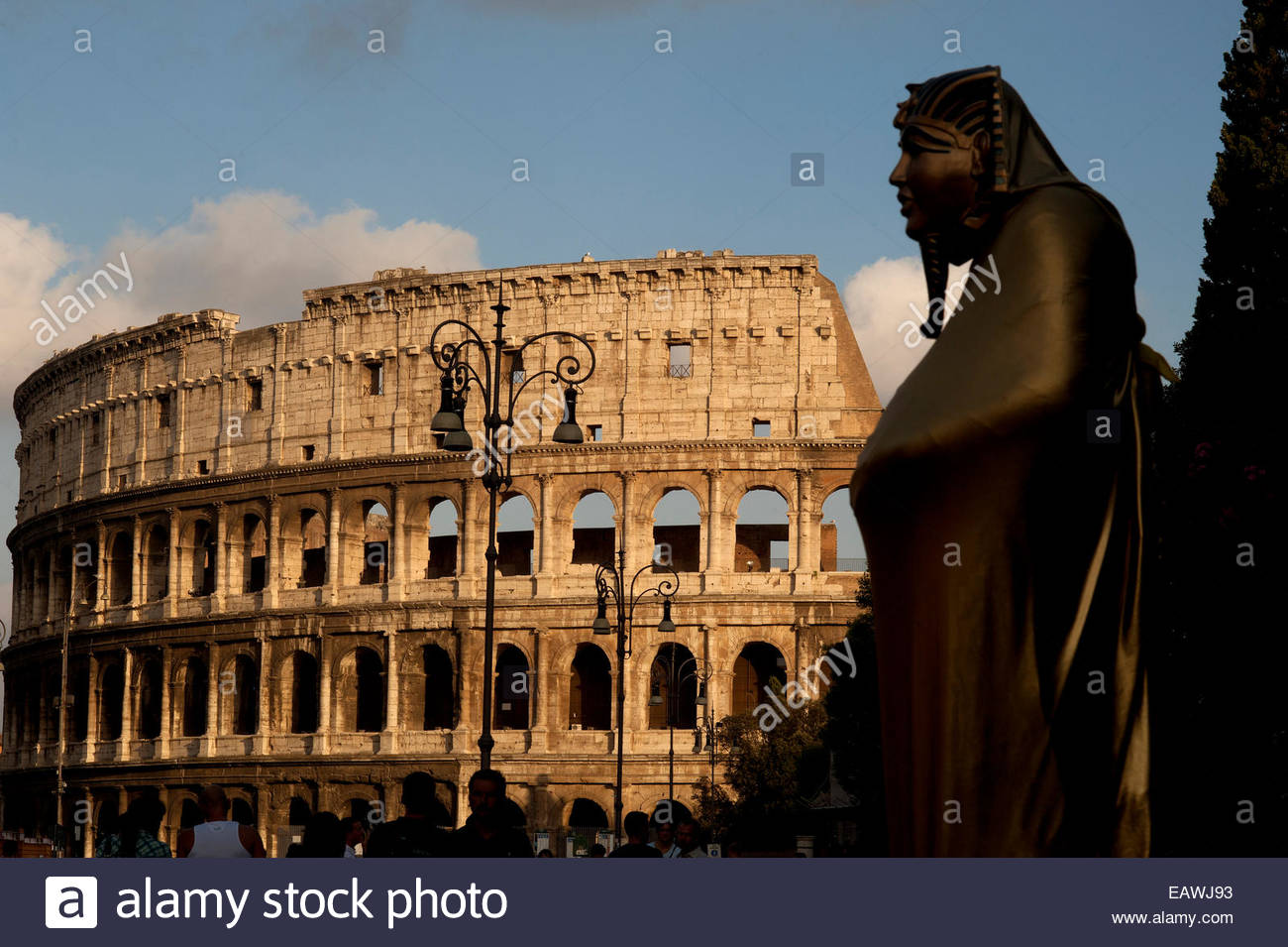 A statue of a pharaoh overlooks the Roman Colosseum. - Stock Image