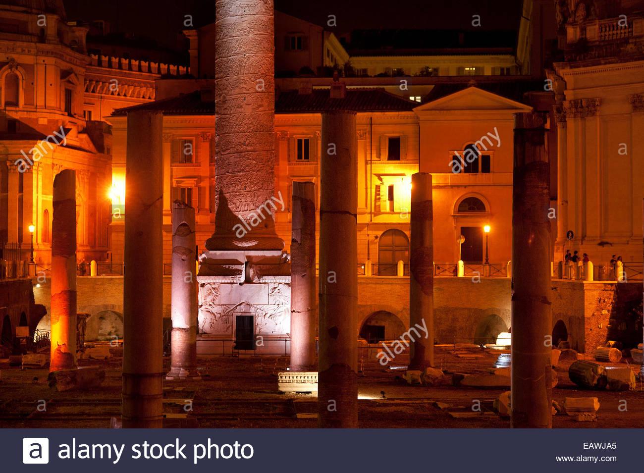 Lights illuminate the base of Trajan's Colum at night. - Stock Image