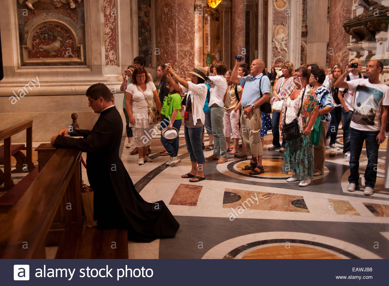 A priest prays while tourists take pictures in Saint Peter's Basilica. - Stock Image