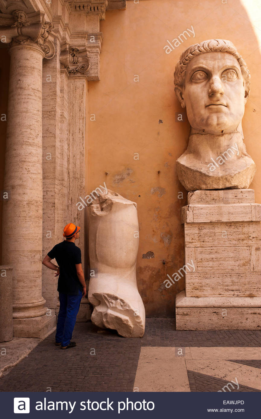 A tourist examines colossal fragments of a statue of Constantine I. - Stock Image