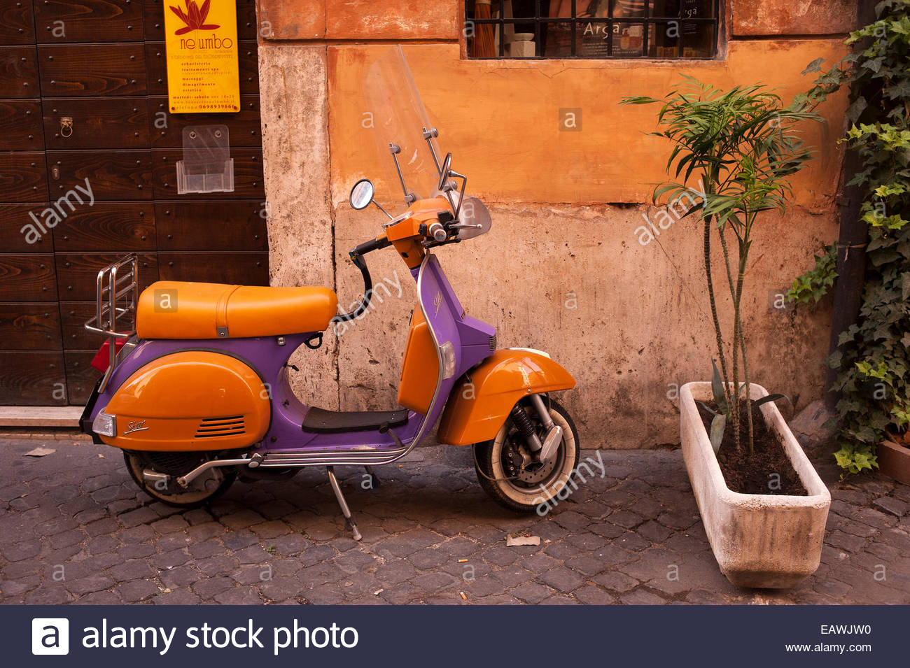 A scooter is parked on a city street in Rome. - Stock Image