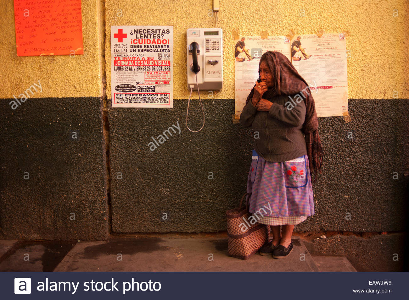 An elderly woman stands near a payphone in Oaxaca, Mexico. - Stock Image