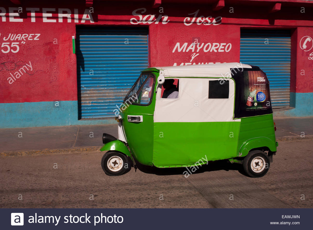 An enclosed motorized tricycle sits parked at a curb in Tlacolula. - Stock Image