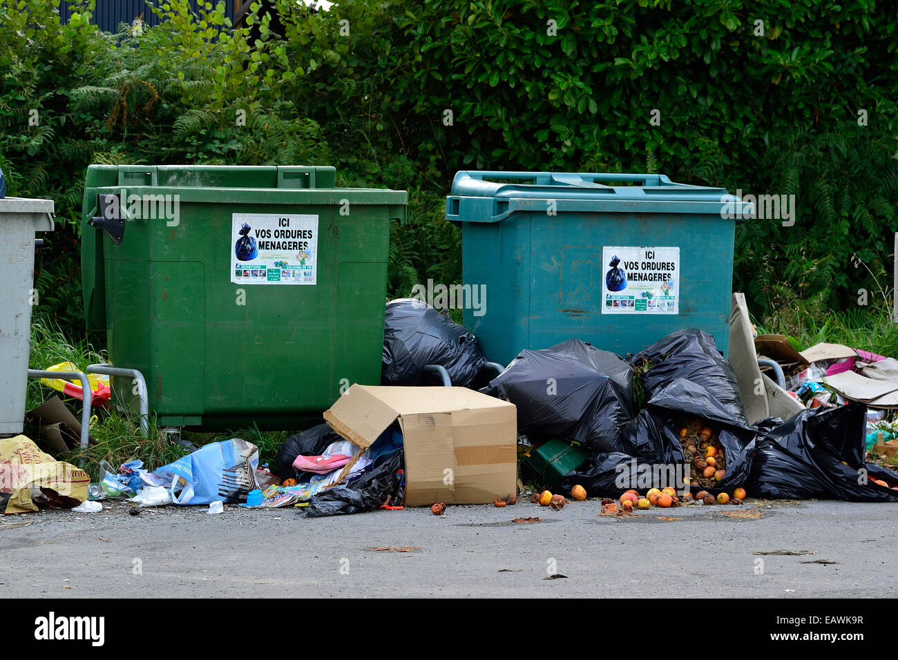 Dumping of waste next to containers for recycling, uncivil practice. - Stock Image