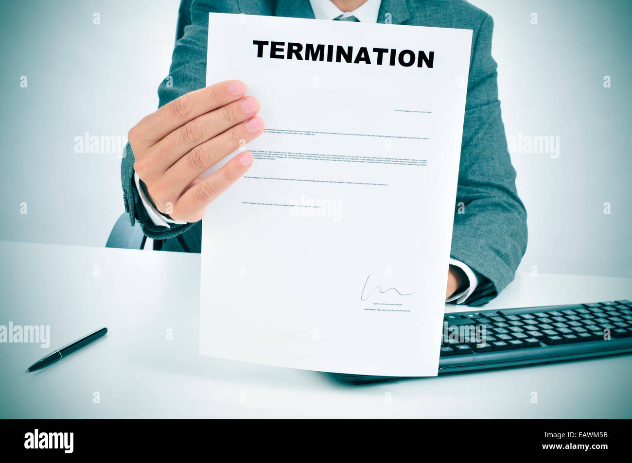 a man in suit in his desk showing a figured signed termination document - Stock Image