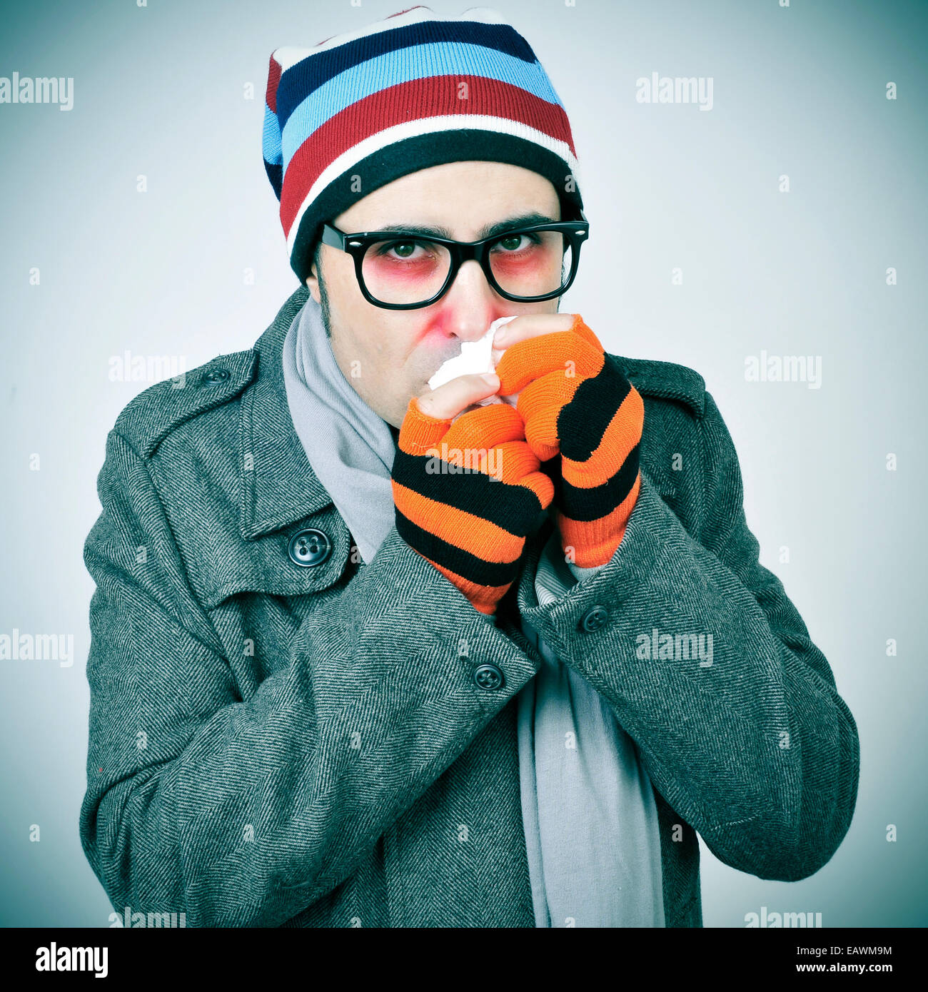 a man with a cold bundled up in a coat, knit cap, gloves and scarf - Stock Image