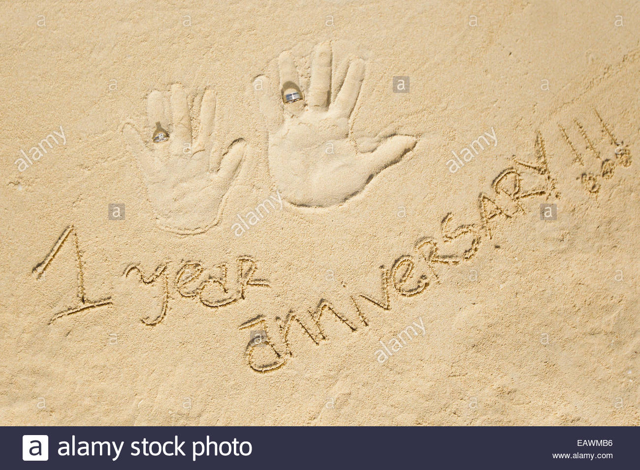 One-year anniversary written in sand next to handprints with wedding rings. - Stock Image
