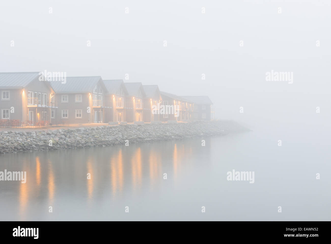 Row of houses along a lake on a foggy evening - Stock Image