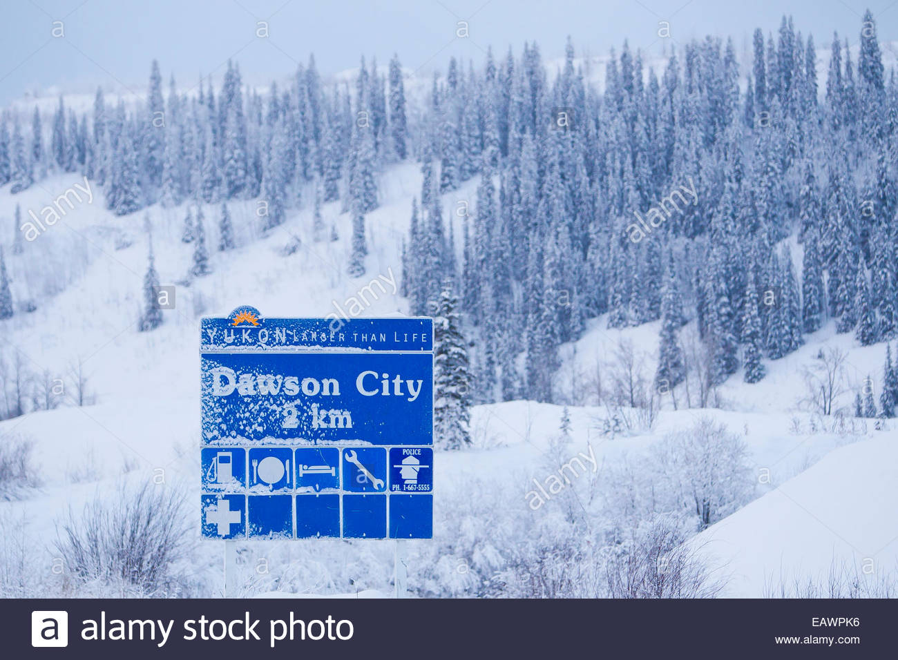 A blue highway information sign for upcoming Dawson City, in a snowy landscape. - Stock Image