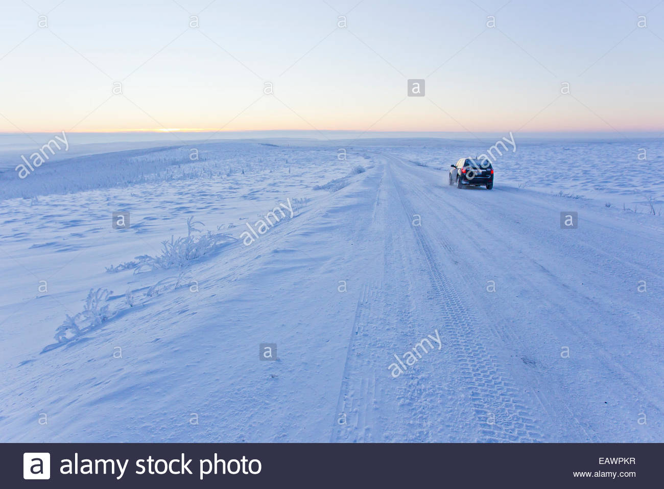 A vehicle parked in a snow and ice covered landscape along the Dempster Highway. - Stock Image