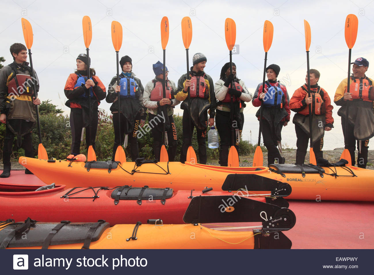 Kayakers with paddles wait to embark on an ecotour. - Stock Image