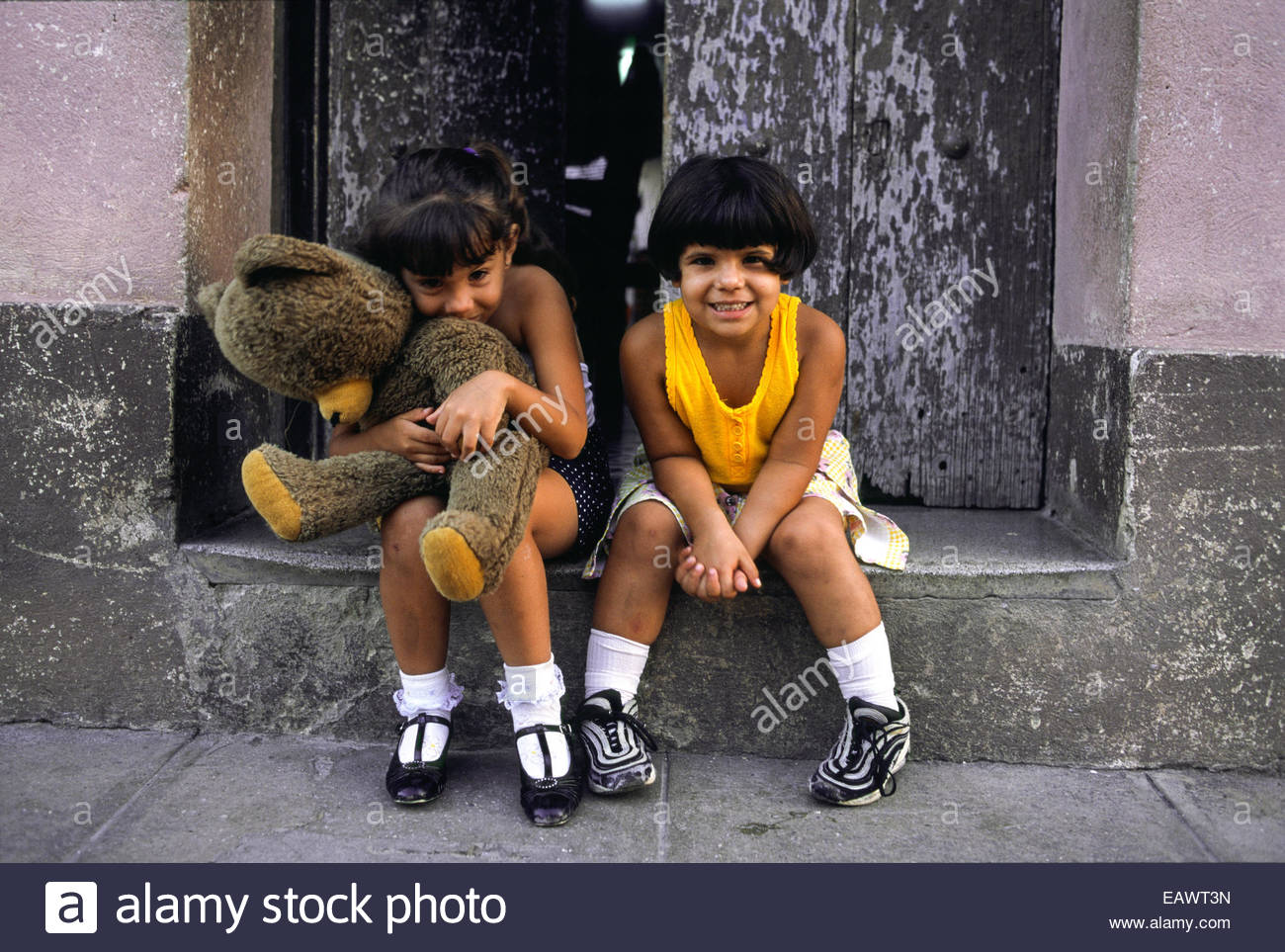 Young girls giggle while sitting in a street side doorway. - Stock Image