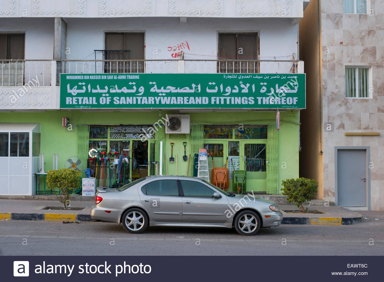 A car is parked outside a store with a poorly translated English sign in Rustaq, Oman. - Stock Image