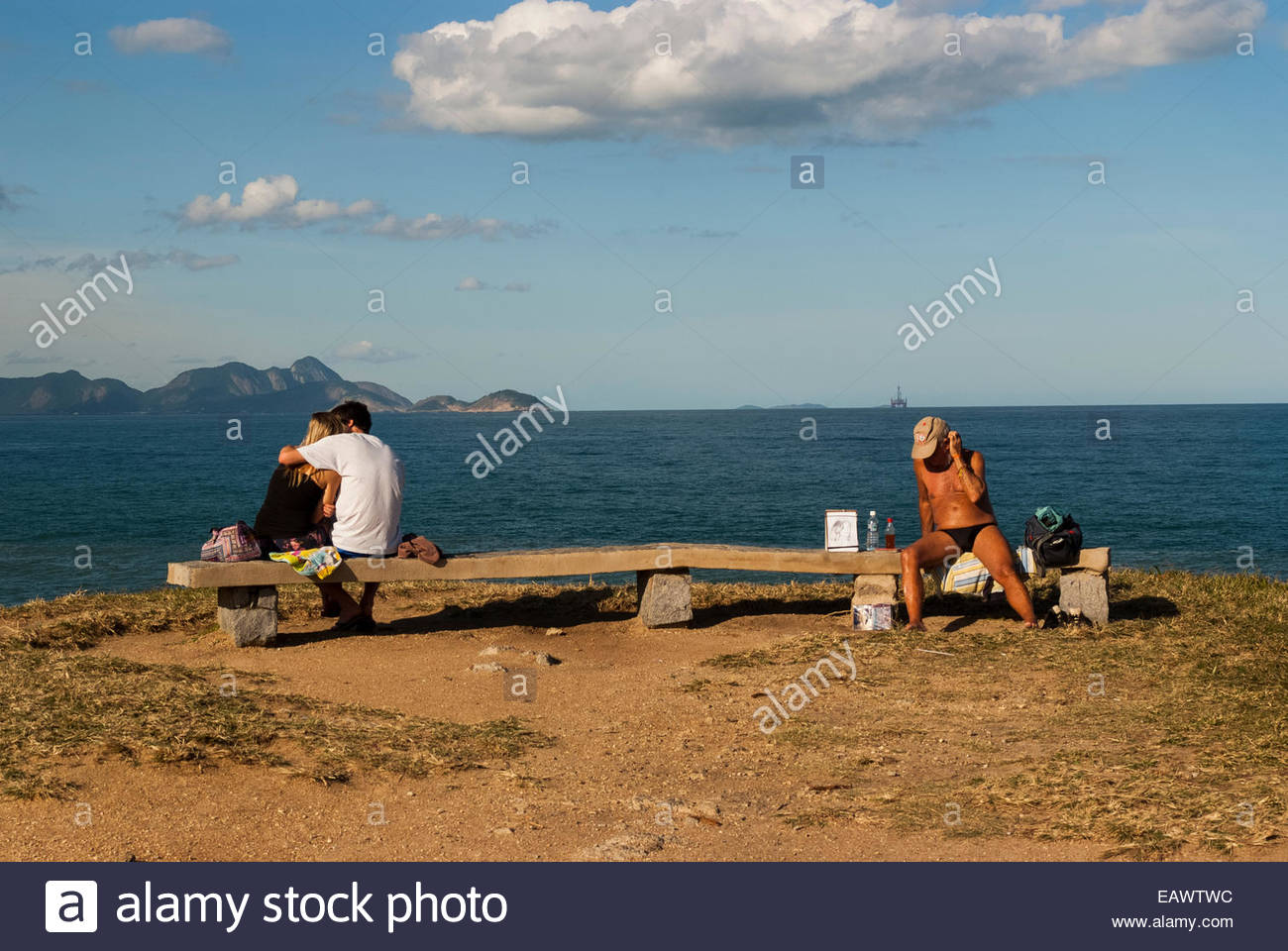 Lovers and a sunbather at Arpoador Rock above the Atlantic Ocean. - Stock Image
