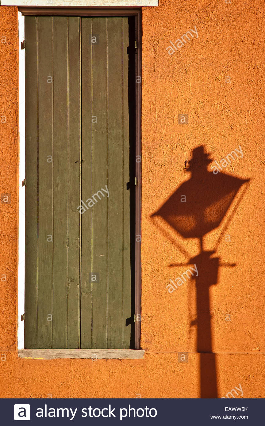A streetlight casts a shadow near a door on a bright orange wall. - Stock Image