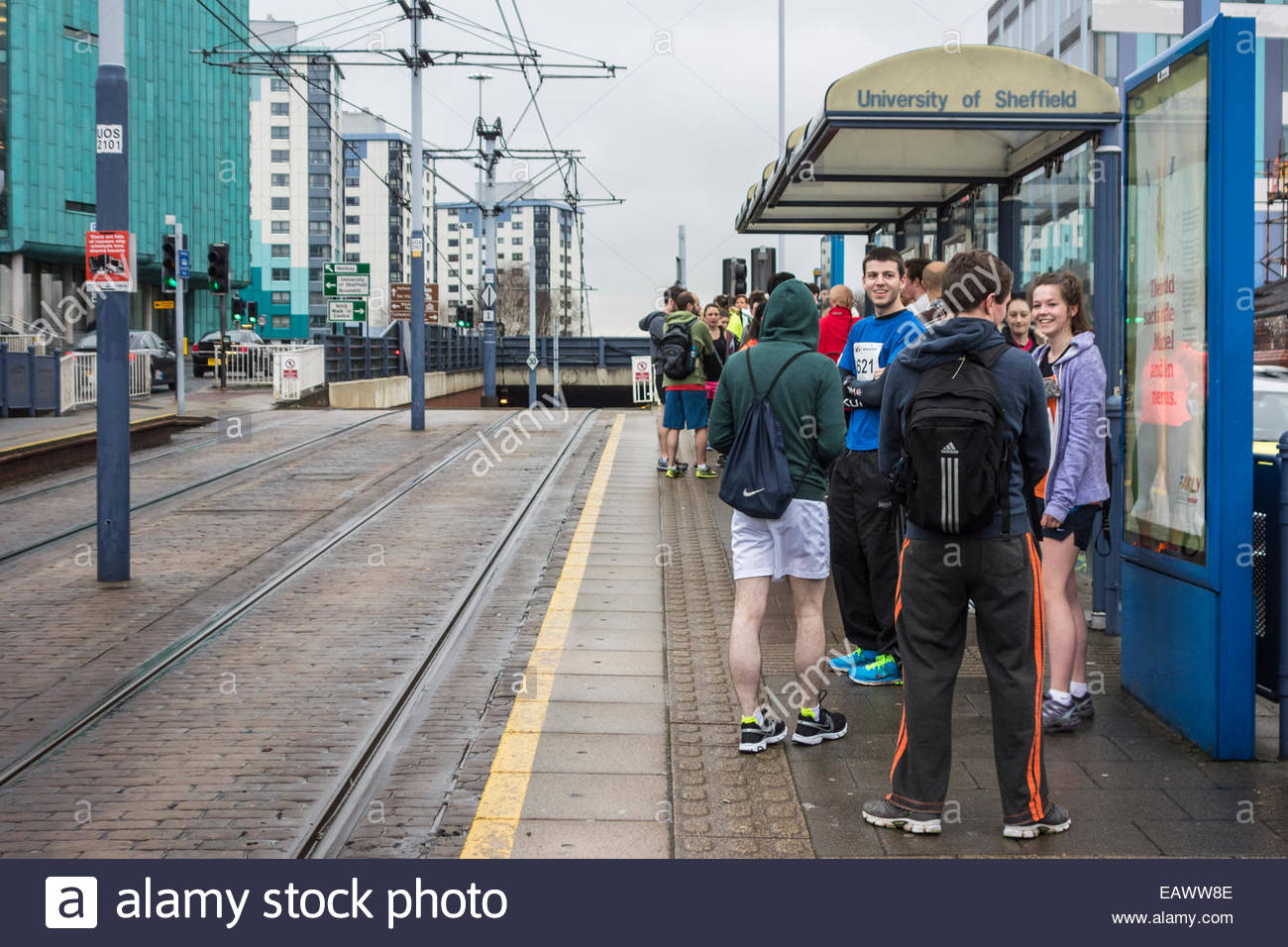 Runners waiting for a tram at the University of Sheffield before the half marathon - Stock Image