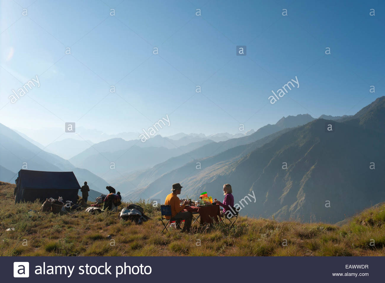 A couple eat breakfast on a secluded hillside in the Juphal valley while trekking in Dolpa, a remote region of Nepal - Stock Image