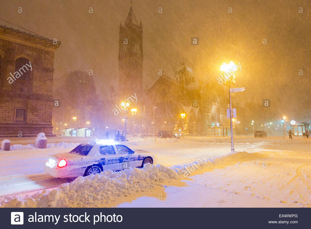 Streetlights illuminate heavy snowfall as a police car cruises city streets during the Blizzard of 2013. Stock Photo