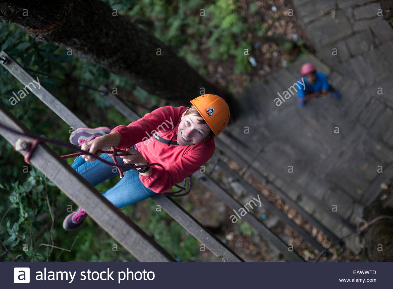 A woman climbs up a giant ladder on a high ropes activity course at The Last Resort in Nepal - Stock Image