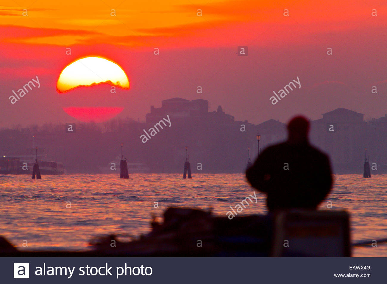 A man in silhouette watches the sunrise over the Grand Canal. Stock Photo