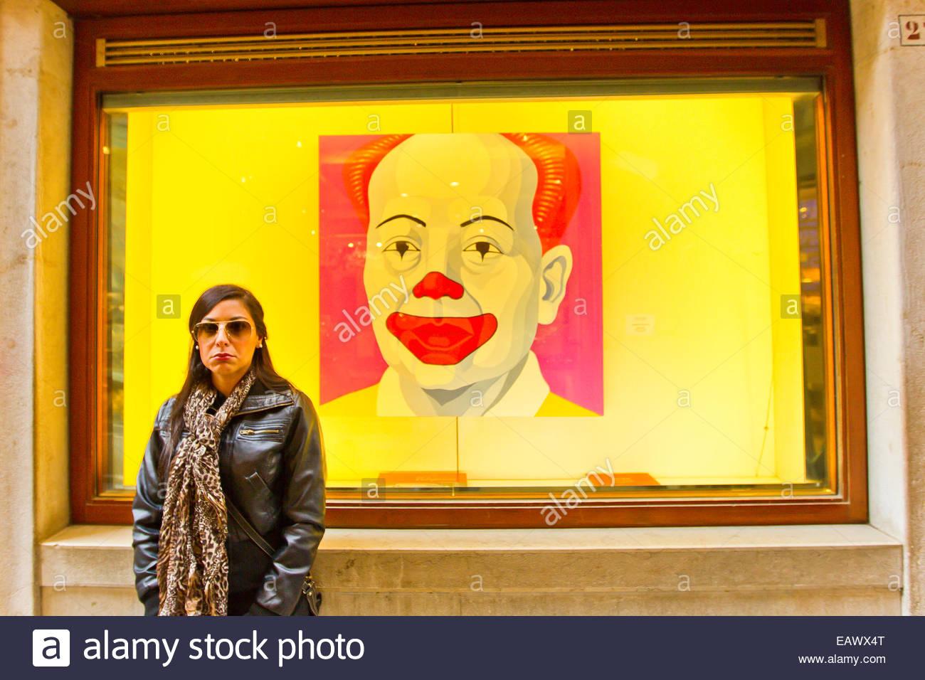 A woman stands in front of a painting of Ronald McDonald in a window display in Venice. - Stock Image