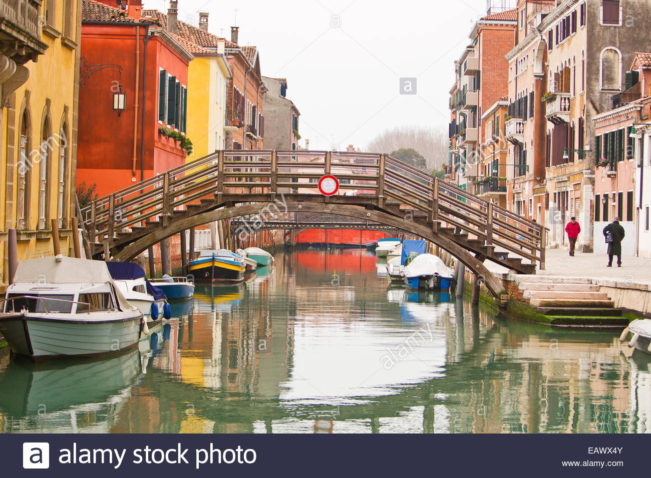 Renaissance era buildings, boats, and a wood bridge cast colorful reflections on a side canal. - Stock Image
