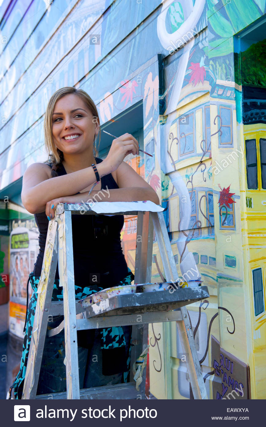 An artist puts the finishing touches on her new 'Mission Makeover' mural. - Stock Image
