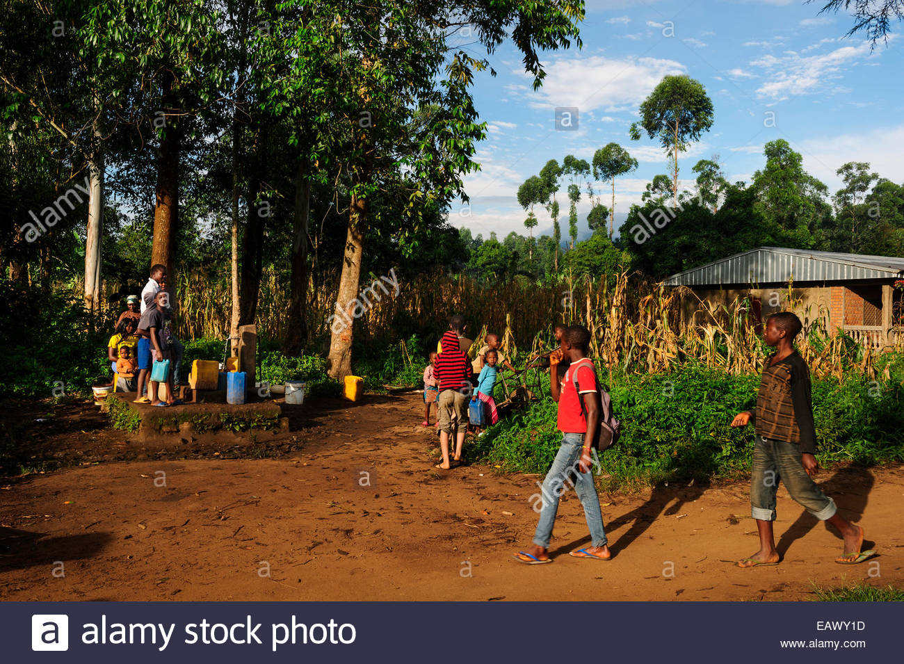 People gather around a village water well. - Stock Image