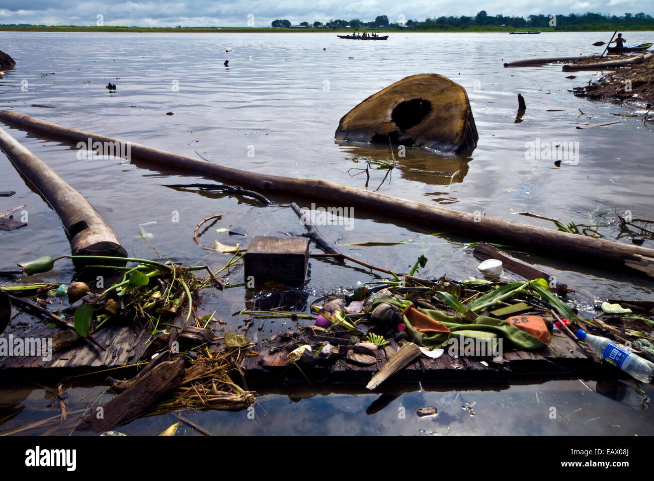 Pollution, logs and rubbish line the shore of the Amazon River near logging mills. - Stock Image
