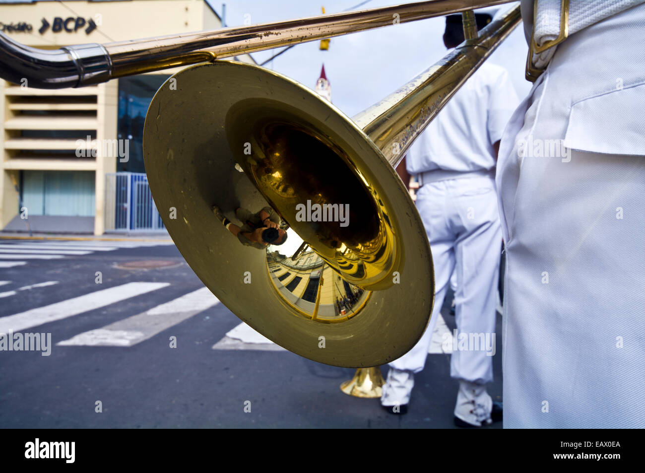 A navy band member with a brass trombone bell and slide at a military parade honoring fallen comrades. - Stock Image