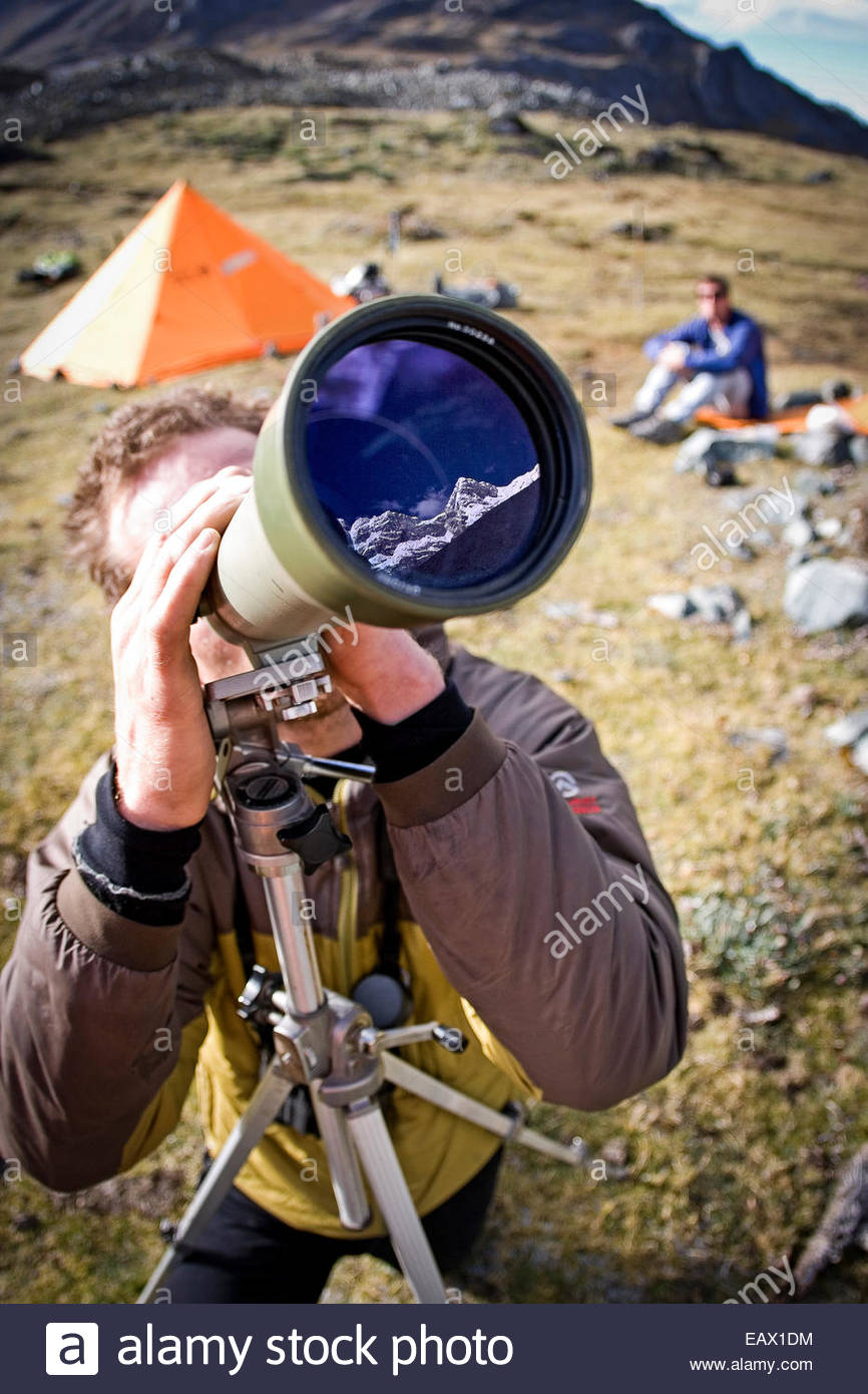 A climber looks through a spotting scope at a mountain in the Cordillera Blanca of Peru. - Stock Image