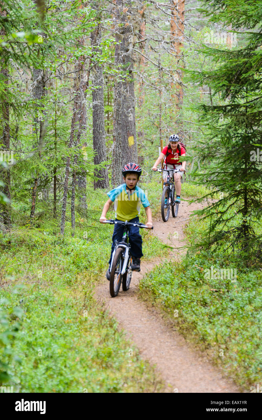 Mother and son riding moutain bikes down a forest path - Stock Image