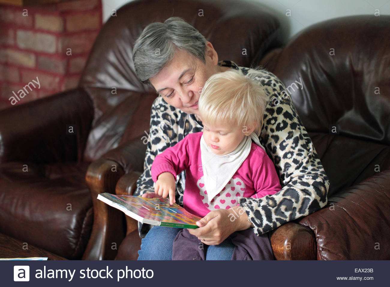 Portrait of a seventeen-month-old baby girl in her grandmother's lap, with a book. - Stock Image