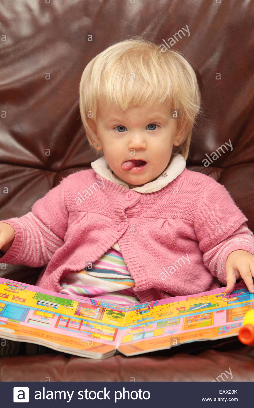 Portrait of an eighteen-months-old baby girl playing with a book. - Stock Image