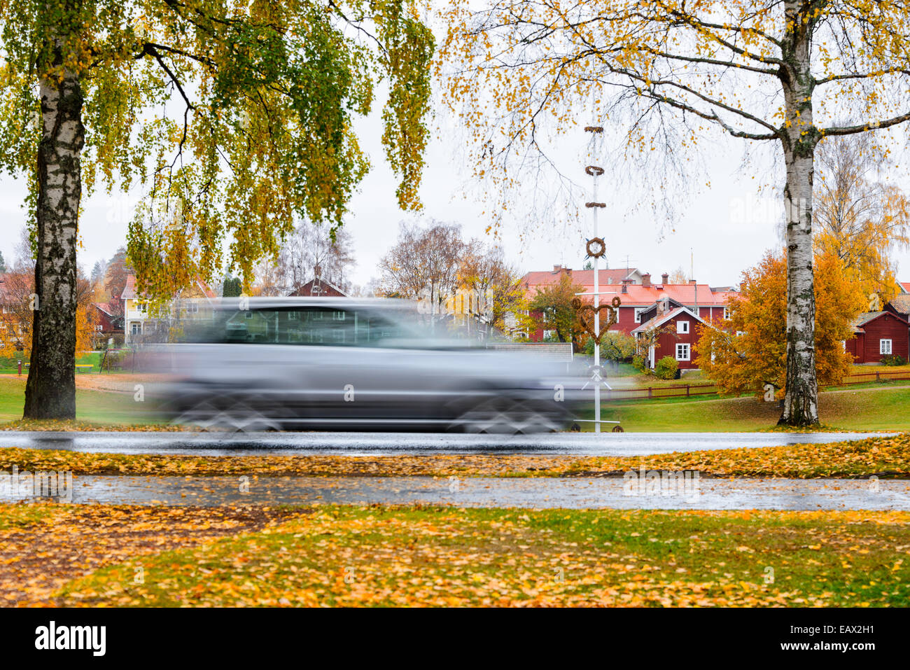 Car moving at speed down a wet road in autumn - Stock Image
