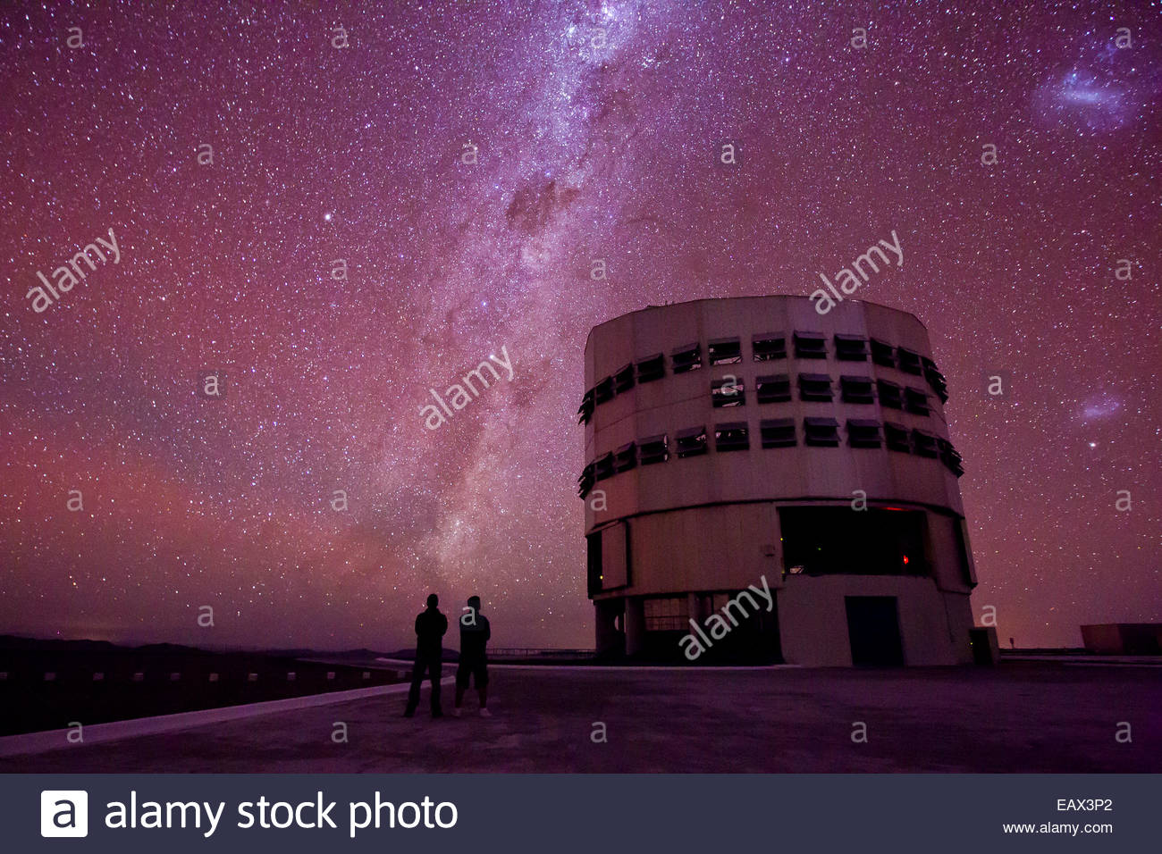 People in silhouette stare at the Milky Way and Magellan galaxies while standing near the Paranal Observatory in - Stock Image