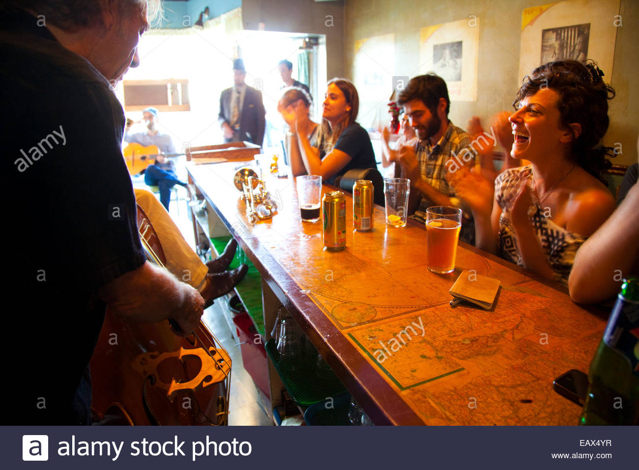 Sunlight streams into the The Communist's Daughter as people enjoy drinks and music at the bar near Queen West. - Stock Image