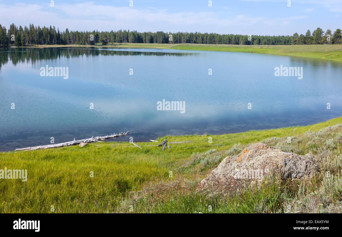 Yellowstone lake on a summer day surrounded by beautiful grassland near West Yellowstone, Wyoming, USA. - Stock Image