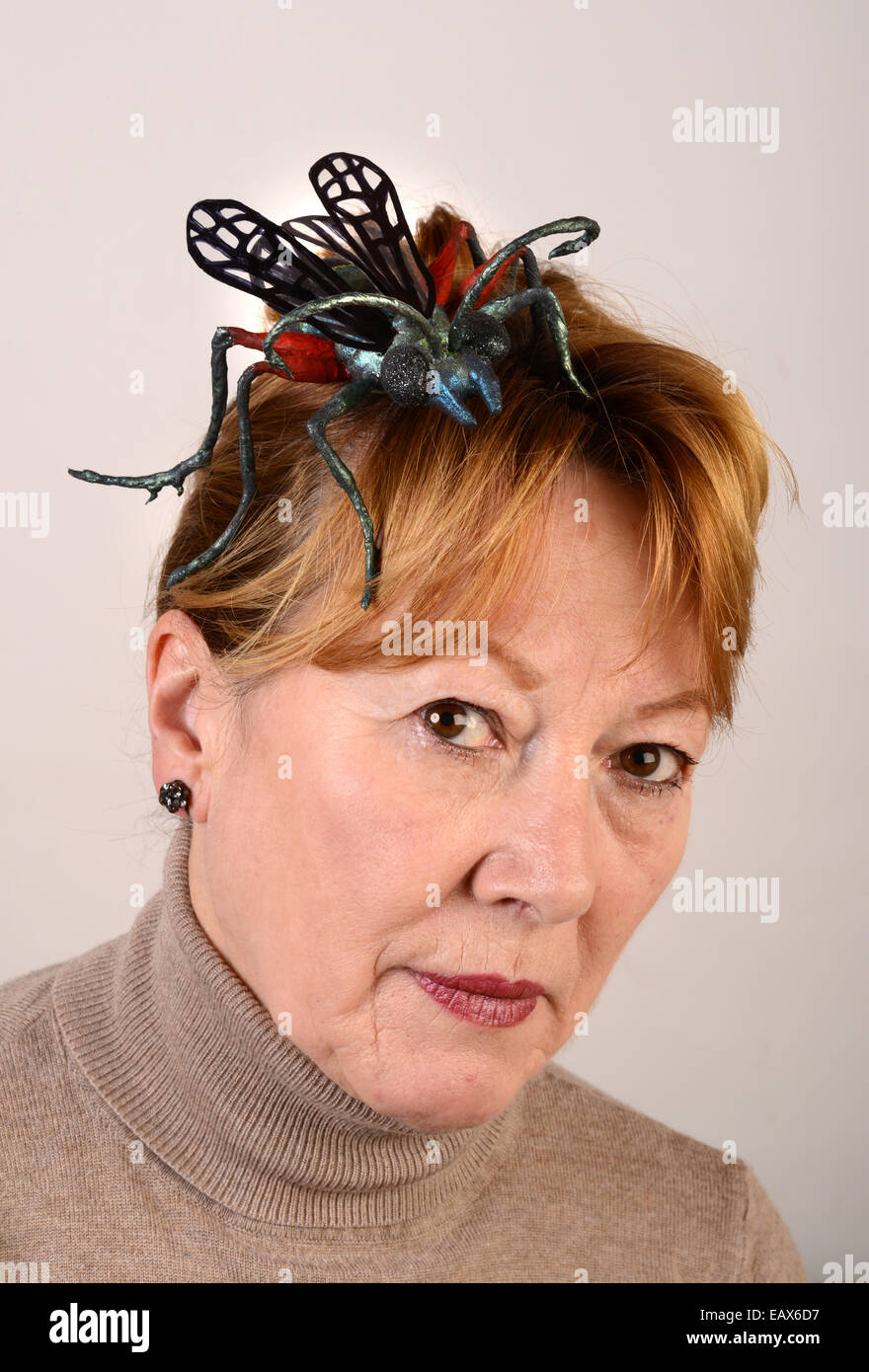 Woman wearing a creative fascinator modelled on the 'Emerald Cockraoch Wasp' or 'Jewel Wasp' made - Stock Image